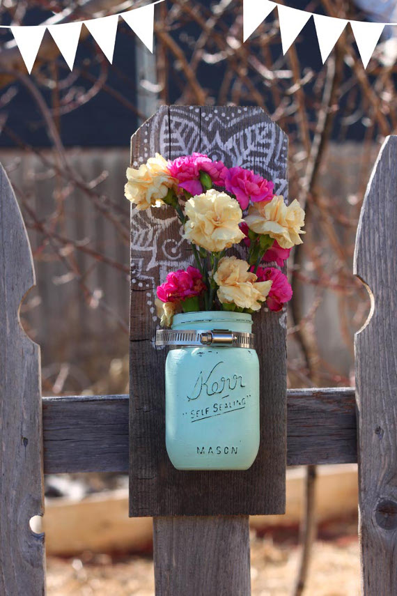 Get ready for spring with a pretty mason jar vase that hangs on a wall!